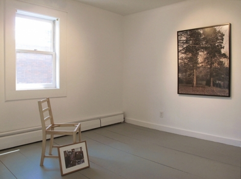 A full view of the 2 works in a small room: a framed image leaning against a white chair and a framed photograph on the wall opposite it