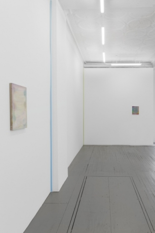 A photograph of the gallery's back quadrant where we see a pale painting by Monick in the foreground at left on the wall. Moving backward on that wall we see 2 ribbon works by Kovachevich (blue, green), then another Monick painting in the background at right.