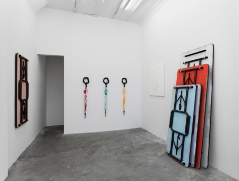 A photograph of the back of the gallery, with table-sculptures leaning against the right wall, 3 umbrellas on the back wall, and a single white painting across from a table work hung on the wall