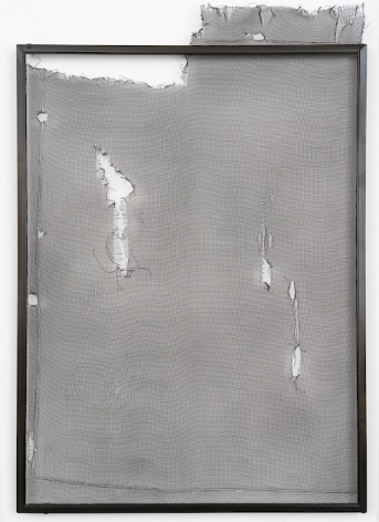 A piece of aluminum screen for a window that is enclosed within a black frame. There are several runs and holes in the screen.