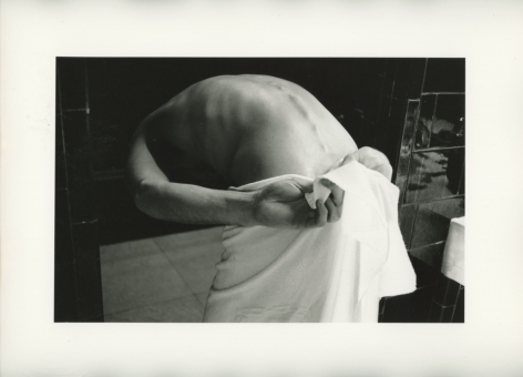 A black and white photograph of a human body bent over, with a towel around their waist, their spine exposed. Minimal details in the background are recognizable.