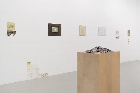 An installation view that includes small magazine clippings piled on a wooden pedestal in the foreground, and 6 mixed-media works installed on the wall.