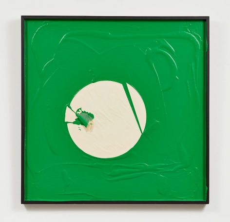 A predominantly green artwork in a white square frame. There are drips and pools of paint. In the middle is a circular shape made of paper, cut in several places but still generally in a circular shape.