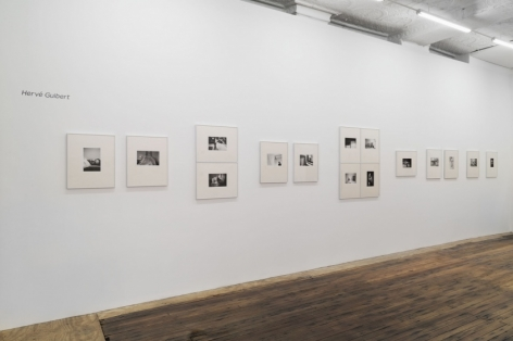 A photograph of the installation of black and white photographs, all in cream mattes. From left to right, there are 2 images in a row, a small space and 2 images stacked; another set of 2 photographs in a row then 4 photographs stacked in a rectangle. At the end of that arrangement are 5 photographs with varied spaces between them. All 15 images are installed on a single wall.