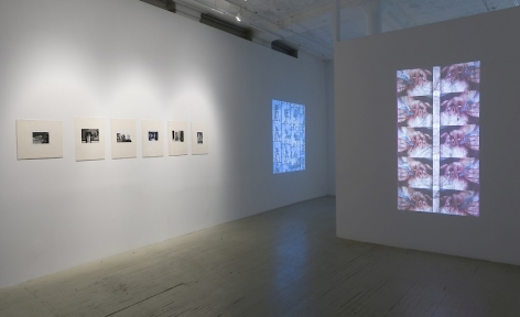 Two videos by Luther price, one on the foreground projected onto a temporary wall and the other is on the wall at left in the gallery. Additionally, the wall at left has 6 black and white photographs by Hervé Guibert in cream mattes.