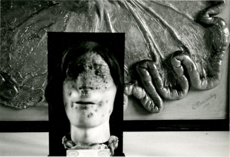 A black and white photograph of a wax figure with a burned face juxtaposed over an abstract, partial sculpture/diorama of body parts.