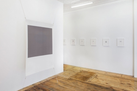 A photograph of the threshold to the back office where we see one gray screenprint, and a row of smaller works framed in white.
