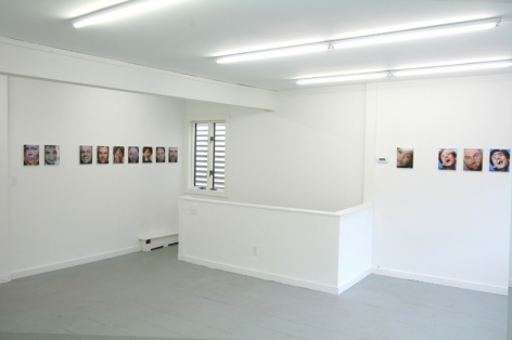 A photograph of 13 images across 2 walls around a corner