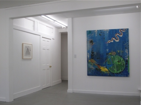 A photograph of a large blue image at right and a small abstract work, framed, at left