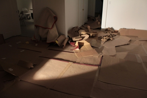 A photograph of the gallery floor. There is nothing on the wall, and panels of cardboard spread throughout the floor. They are used.