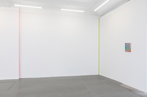 A photograph of the back quadrant of the gallery that depicts two ribbon artworks in the corners (pink at left, lime green at right). On the right wall is a small multicolor painting by Monick.