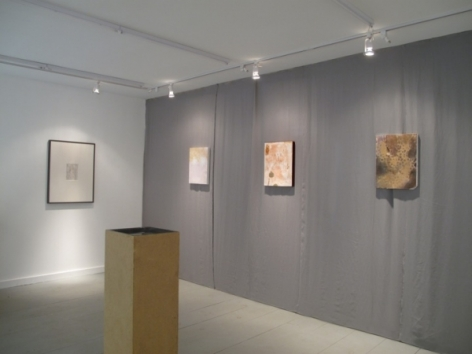 A photograph of 3 flat works on the right on a gray wall, with a pedestal in the middle of the room, and a framed work on the far wall