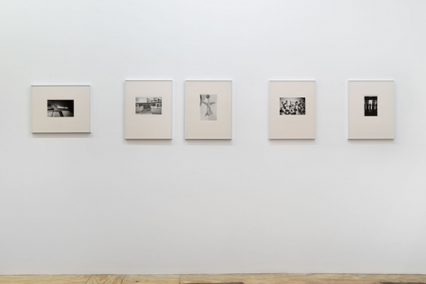 A photograph of the installation with 5 photographs in a row, all installed in cream mattes and silver frames.