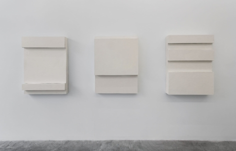A photograph of 3 white rectangular sculptures installed on the wall