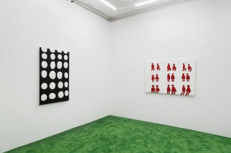 A photograph of the back gallery with 2 artworks: at left is a black-and-white polka dot work; at the right is a group of 9 pairs of figures found on bathroom doors on a white ground.