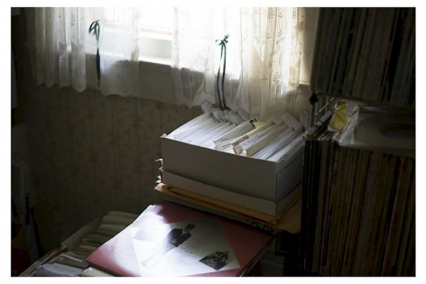 A photograph of an interior domestic scene with a box of letters centrally located. There are records on a shelf at right, and a window with sunshine coming through it just above the box of letters.