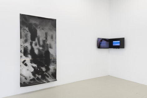an installation view of the show showing the large photogram and a video installation of two monitors installed to a corner of the gallery, edge to edge