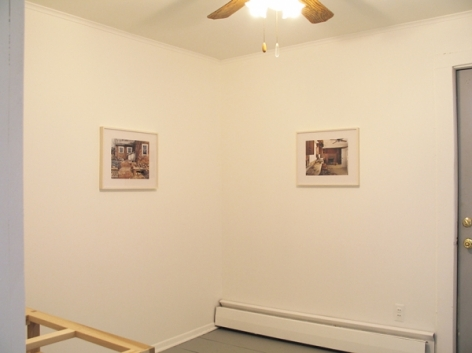 A photograph of 2 photographs framed in white from across the room