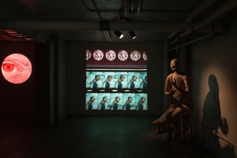 A photograph of the gallery's basement with one film being projected on the back wall. At right is a bronze sculpture seated on a stool. At left is a circle that encloses a red eyeball, seemingly illustrated.