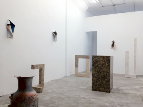 A photograph of the gallery with 5 sculptures installed on the ground and 3 photographic works on 2 walls