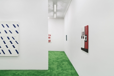 A photograph of the gallery with an excerpt of the white and blue work at left. There is a path to the back office gallery with a red, black, and white artwork on the right, and 2 other works excerpted in the background.