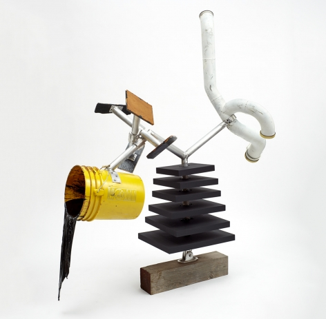 A mixed media sculpture of a yellow bucket, resin, a white tube, and layered wooden slabs