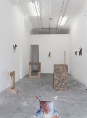 A photograph from the front of the gallery that visualizes 5 sculptures on the ground and 4 photographic works on 3 walls