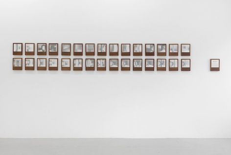 An installation of 30 photo book-objects by Dayanita Singh installed on a white wall