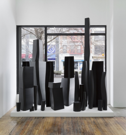 A photograph of a sculpture, installed upon a white plinth in front of the window of the gallery. The 35 elements of this piece are of varying heights and widths, with a sheen in the light.