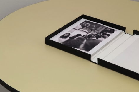 An photograph of an open binder with a single black and white photograph.