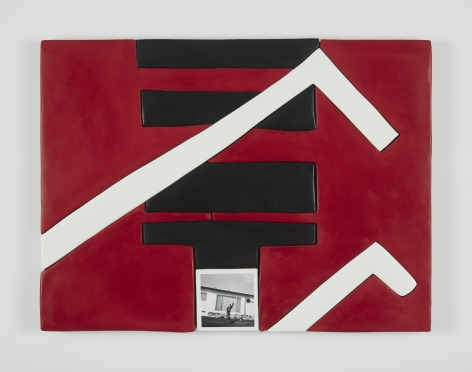 An abstract work with a red background, black and white shapes, and a small black and white photo at the bottom-center
