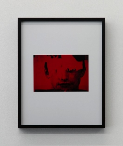 An image in red and black of a boy's face, framed in black