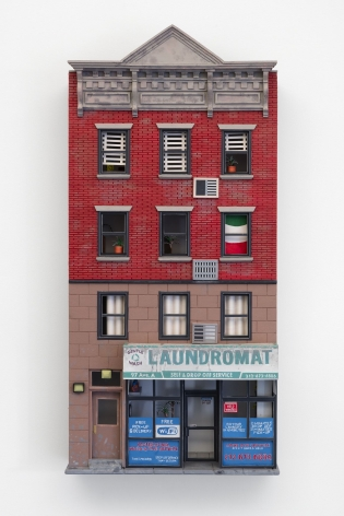 A sculpture made of foam and paper that depicts a building facade with a laundromat on the first floor, and apartments on the 3 floors above it. Half the building is red brick; the other half is beige stone.