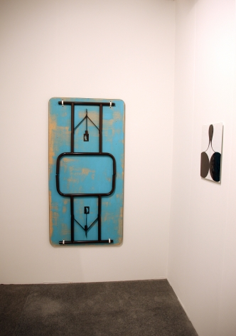 A folding table hung on the wall, painted blue, and one of Müller's enamel paintings at right