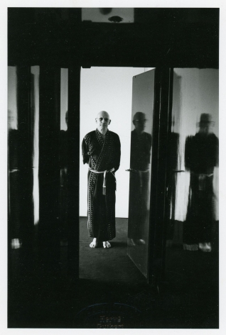 A black and white photograph of Michel Foucault in a doorway, dressed in a kimono