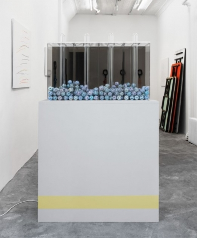 A photograph of a vitrine filled with blue balls. The white pedestal has a yellow stripe hear the bottom.