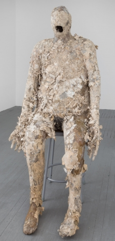 A sculpture of a nondescript sitting body, mouth open, hands by its side, with wisps of paper coming off of the body.