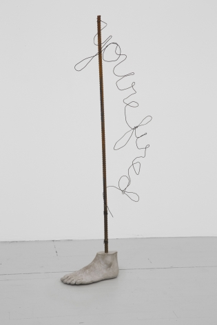 "A cement foot attached to a steel rebar with the words ""you're fired"" written in script, in wire, hanging to the right of the rebar."