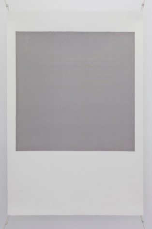 A photograph of a silkscreen on paper. The shape resembles a polaroid (white space on the bottom and a white frame around a central grey space). The grey space in the middle of the work has text in faint gold letters, illegible from a distance.