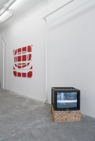 A photograph of a monitor installed on a pedestal and a large red/white work on the wall behind it.