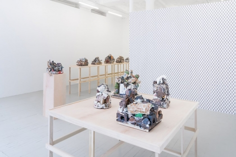 A photograph providing the view of the gallery from the front window. The square raw table with 4 ceramic sculptures is in the foreground, a single pedestal with a ceramic sculpture is in the midground, and in the background we see a long raw platform with 4 visible sculptures upon it. We also see the chainlink wallpaper on the temporary wall jutting from the right of the photo.