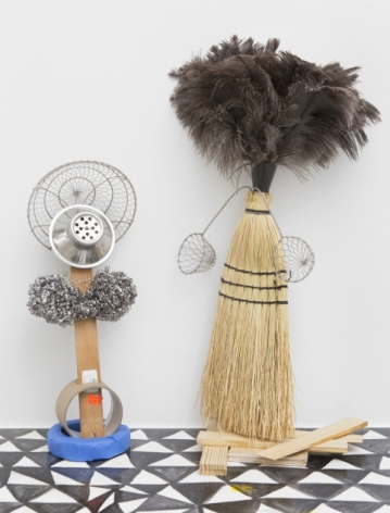 A photograph of two mixed media sculptures: on the left is a work made of tape rolls, steel wool, and 2 colanders; at right is a sculpture made of the head of a broom and a feather duster at the top with two small strainers jutting from either side.