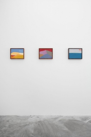 A photograph of 3 technicolor abstract landscapes hung on the wall