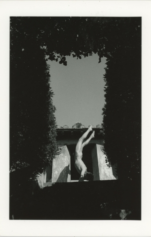 A black and white photograph of a naked man, resting on his forearms, legs in the air. A frame within the image is created by towering hedges. Behind the figure we see a window and the wide open sky.