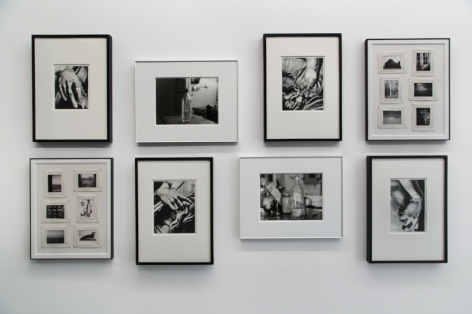 A straight-on photograph of 8 black and white images, framed, in a salon hang.