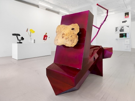 An installation view of Harry Dodge's large purple sculpture, with bronze sculptures in the background on a plinth