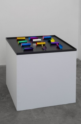 A sculpture of 12 pieces of paper on a black stage, on a white pedestal