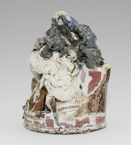 A mixed ceramic sculpture with a round base that moves to an apex. At the peak of the small sculpture is a silver volcanic mass, beneath which is a ceramic piece that resembles a crumbles bedsheet. Near and beneath the white mass is stone with decals (lottery numbers, cigarette logos) applied in red.