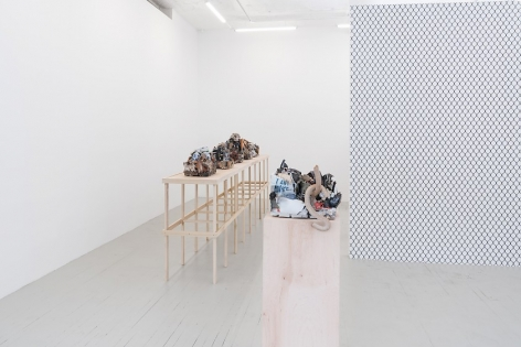 A photograph of the chainlink fence wallpaper at right, jutting to the left from the right. There is a raw wood pedestal with a single ceramic sculpture, and a long raw wood platform with a single row of 5 ceramic sculptures.