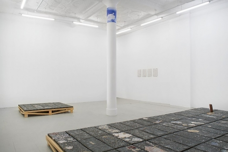 Installation image that shows 4 white tiles in the distance, an artwork on the floor made of black clay, and half of the large ceramic sculpture installed on the floor in the foreground